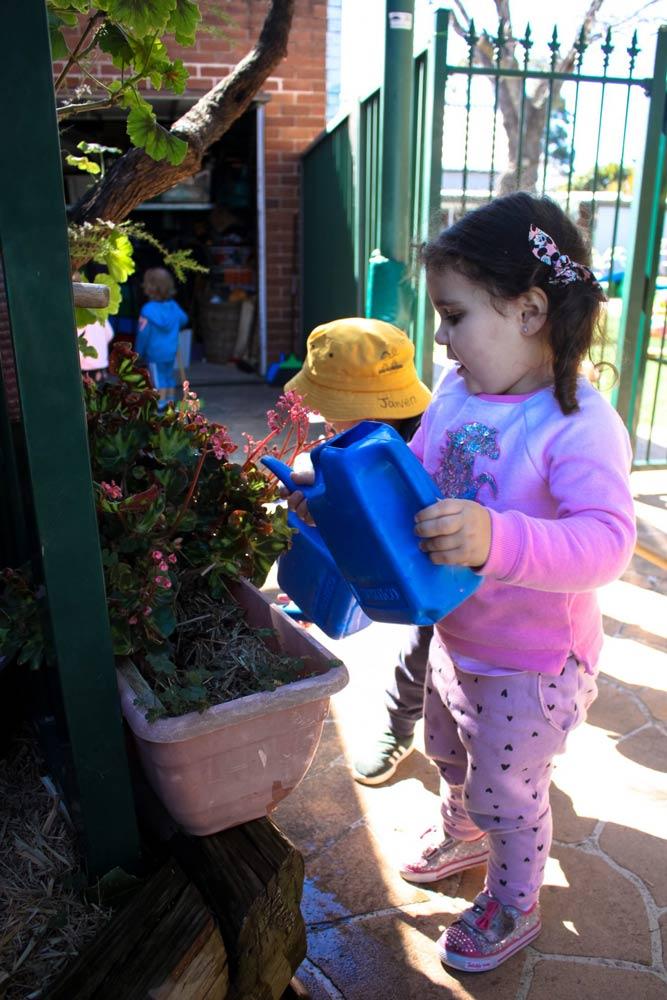 Beverly Montessori child watering plants