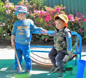 Beverly Montessori kids with brooms