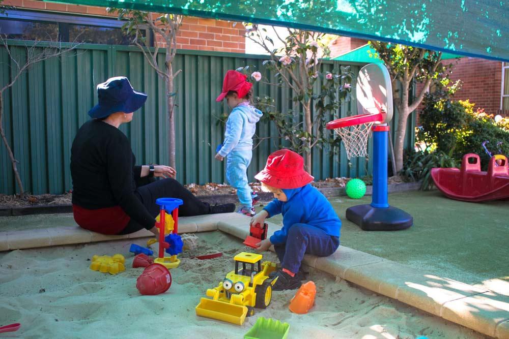 Beverly Montessori teacher and kids in sandbox